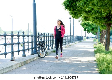 Full length shot of young woman running on the street.