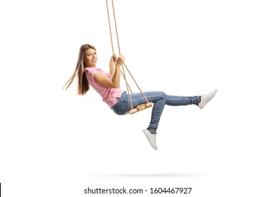 Full length shot of a young woman with long hair swinging on a wooden swing isolated on white background