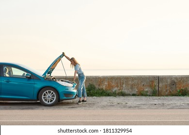 Full length shot of young woman looking under the hood of her broken car, trying to repair it on her own while standing alone after car breakdown on the road side, Side view, Horizontal shot