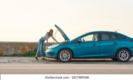 Full length shot of young woman looking under the hood of her broken car, trying to repair it on her own while standing alone after car breakdown on the road side, Side view, Web Banner