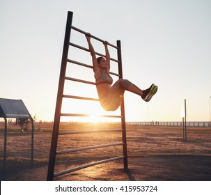 Full length shot of young woman exercising on wall bars with her legs up. Fitness woman exercising her abs with hanging leg raises.