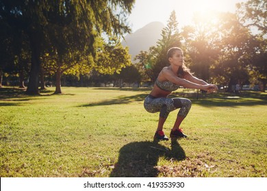 Full length shot of young woman practicing squats in park. Horizontal shot of a young woman exercising outdoors on a nice summer day.