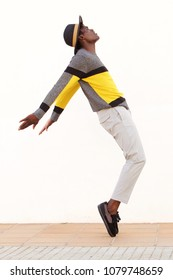 Full length side portrait of african male dancer standing on his tip toes making a cool dance pose