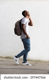 Full length side portrait of a cheerful male student walking and talking on cell phone