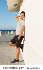 Full length side portrait of fitness man leaning against wall outside