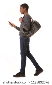 Full length side portrait of happy african american man walking with mobile phone and bag