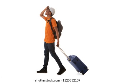 Full length side portrait of happy african american male traveler walking with suitcase against isolated white background