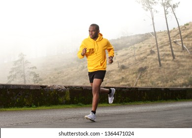 Full length side portrait of healthy young african american man running on street