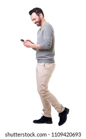 Full length side portrait of man walking with mobile phone