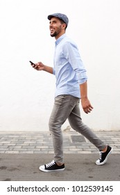 Full length side portrait of smiling man walking with cellphone against white wall