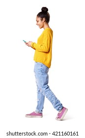 Full length side portrait of smiling young woman walking and looking at mobile phone on white background