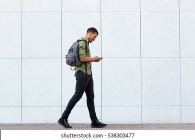 Full length side portrait of smiling man walking with backpack smart phone and headphones