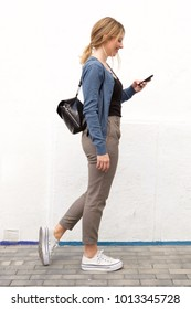 Full length side portrait of young woman walking with mobile phone against white wall