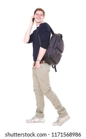 Full length side portrait of young male student walking on isolated white background with bag and mobile phone