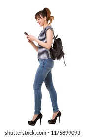 Full length side portrait of young woman walking with mobile phone and bag against white background