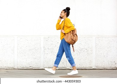 Full length side portrait of young urban woman walking and talking on mobile phone