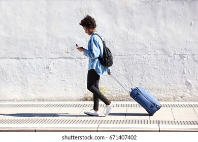 Full length side portrait of young african woman walking on railway platform with suitcase and using mobile phone