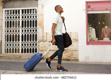 Full length side portrait of young male traveler walking on street with suitcase