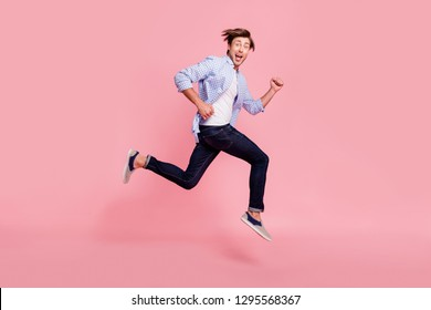 Full length side profile body size photo of jumping high he his him handsome run fast look oh yeah yes expression hair fly flow wearing casual jeans checkered plaid shirt isolated on rose background