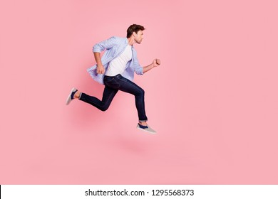Full length side profile body size photo of jumping high he his him handsome run fast  look empty space need win victory winner wearing casual jeans checkered plaid shirt isolated on rose background