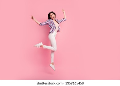 Full length side profile body size photo funny beautiful her she lady jump high holiday fists raised wear shoes casual checkered plaid shirt white jeans denim clothes outfit isolated pink background