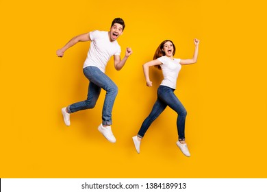 Full length side profile body size photo funky she her he him his pair jumping high hurry shopping raised fists yell scream shout loud wear casual jeans denim white t-shirts isolated yellow background