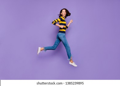 Full length side profile body size photo beautiful she her lady cheerful jump high flight hurry shopping sale discount mall store wear blue yellow striped pullover isolated violet purple background