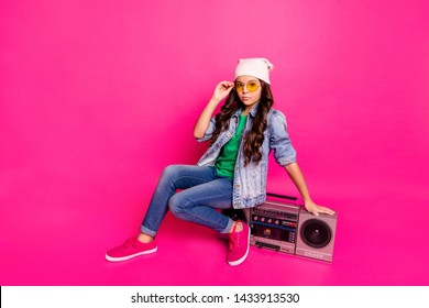 Full length side profile body size photo beautiful little she her curly brunette lady sit old-fashioned tape audio recorder wear yellow sun specs hat casual jeans denim jacket isolated pink background