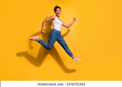 Full length side profile body size photo funny she her dark skin model lady jumping high champion rush sale discount shop wear casual jeans denim pants trousers tank-top isolated yellow background