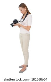 Full length side view of a beautiful female photographer over white background