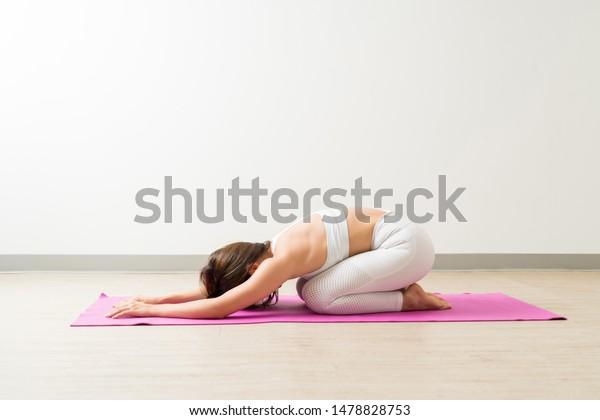 Full length side view of brunette female in sportswear practicing Balasana at fitness studio