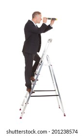 Full length side view of businessman on ladder looking through telescope over white background