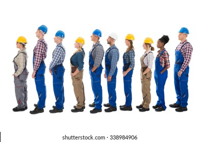 Full length side view of carpenters standing in line against white background