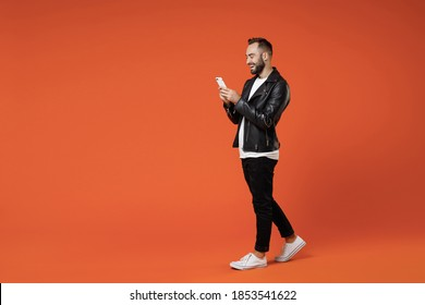 Full length side view cheerful young bearded man in basic white t-shirt black leather jacket standing using mobile cell phone typing sms message isolated on orange colour background studio portrait