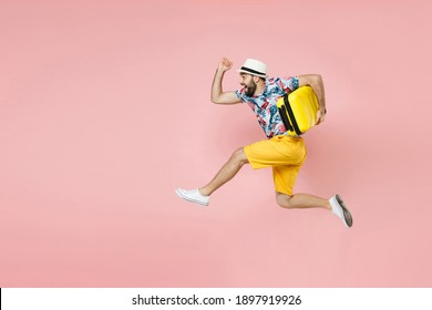 Full length side view of cheerful traveler tourist man in summer clothes hat jumping running hold suitcase isolated on pink background. Passenger traveling on weekend. Air flight journey concept