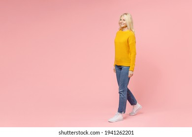 Full length side view of cheerful elderly gray-haired blonde woman lady 40s 50s years old in yellow basic sweater walking going looking aside isolated on pastel pink color background studio portrait