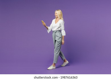 Full length side view cheerful laughing elderly gray-haired blonde woman lady 40s 50s in white dotted blouse using mobile cell phone typing sms message isolated on violet background studio portrait