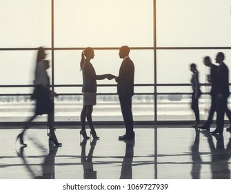 Full length side view concentrated colleague greeting with young woman in lounge zone. Focused affiliates during break concept