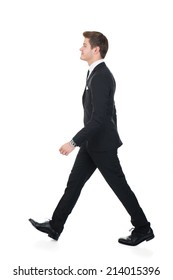 Full length side view of confident businessman walking against white background