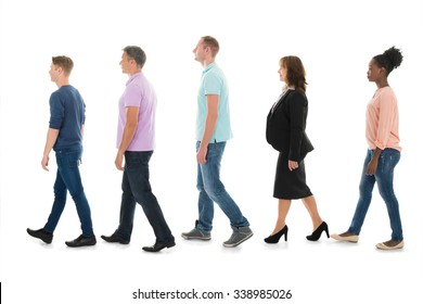 Full length side view of creative people walking with manager in row against white background