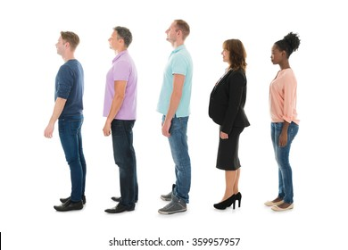 Full length side view of creative people standing with manager in row against white background