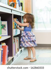 Full length side view of cute girl choosing book from school library