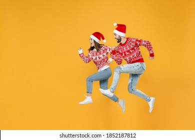 Full length side view of excited young Santa couple friends man woman in red sweater Christmas hat jumping like running isolated on yellow background. Happy New Year celebration merry holiday concept