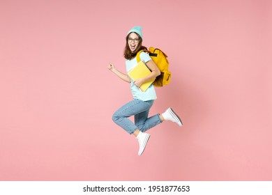 Full length side view of excited young woman student in blue t-shirt hat glasses backpack hold notebooks jump isolated on pink background studio. Education in high school university college concept