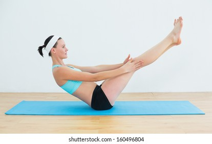 Full length side view of a fit young woman doing the boat pose on yoga mat in fitness studio