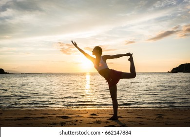 Full length side view of a fit woman practicing on the beach. The standing bow pulling pose for muscular strength and flexibility during summer vacation in Indonesia