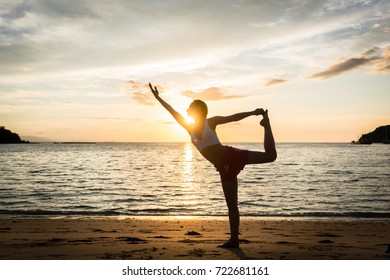 Full length side view of a fit woman practicing on the beach the standing bow, pulling pose for muscular strength and flexibility during summer vacation in Indonesia