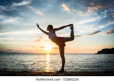 Full length side view of a fit woman practicing on the beach the standing bow pulling pose, for muscular strength and flexibility during summer vacation in Indonesia