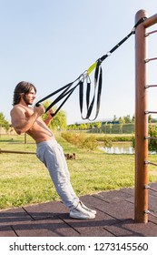 Full length side view of a handsome fit young man exercising biceps curls with suspension trainer outdoor in the park; trx suspension training concept