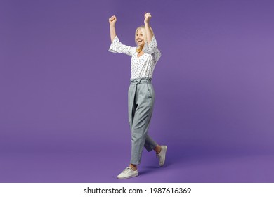 Full length side view happy joyful elderly gray-haired blonde woman lady 40s 50s in white dotted blouse doing winner gesture looking aside isolated on bright violet color background studio portrait
